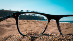 A closeup shot of beach viewed from the lenses of black glasses