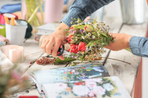 Florist at work: young female hands making fashion modern bouquet of different flowers