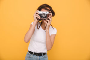 Portrait of a young brunette girl making a photo with a retro camera while standing isolated over yellow background