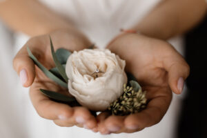 Tender eustoma flower with engagement ring inside with tiny diamond in hands of bride